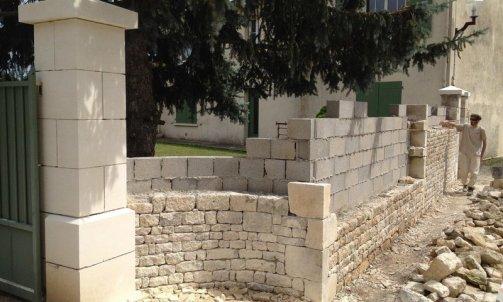 Création d'un mur de clôture en pierre , pose de pilier en pierre .