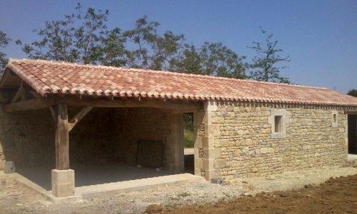 Construction d'un garage habillage pierre et pose d'une toiture traditionnelle .